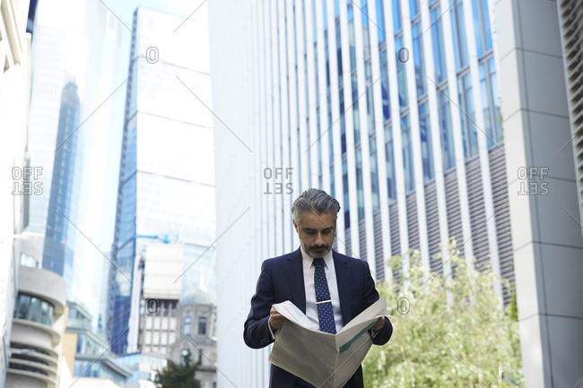 Entrepreneur reading newspaper outside office in city