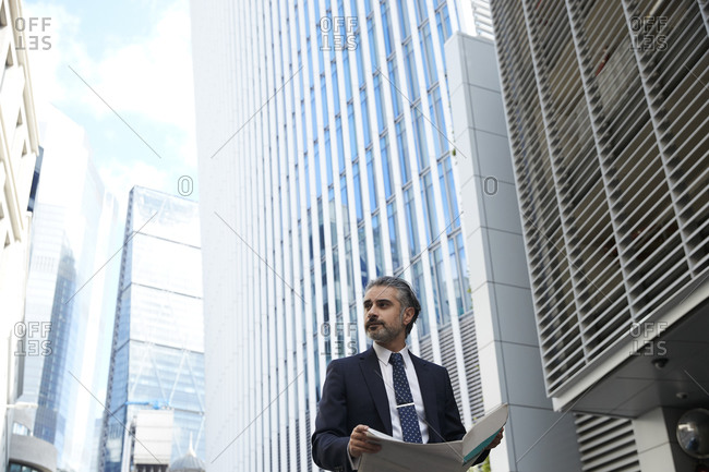 Entrepreneur with newspaper looking away outside office building in city