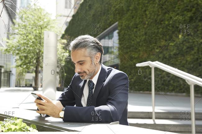 Businessman texting through phone in city