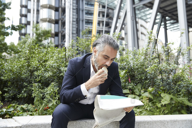Entrepreneur reading newspaper while eating food in city