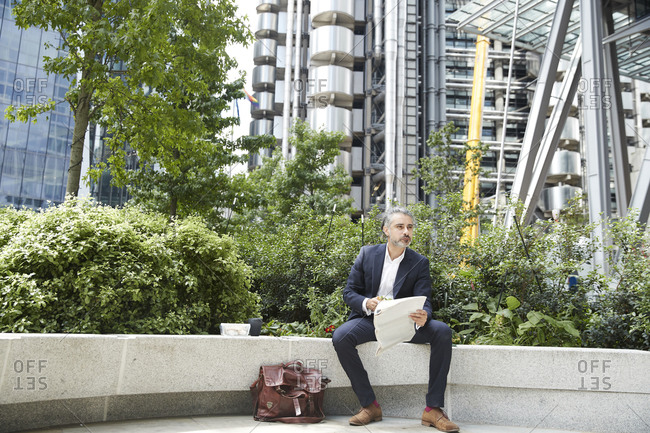 Entrepreneur with newspaper looking away while sitting on retaining wall in city