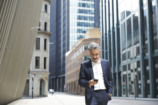 Businessman texting through mobile phone in city