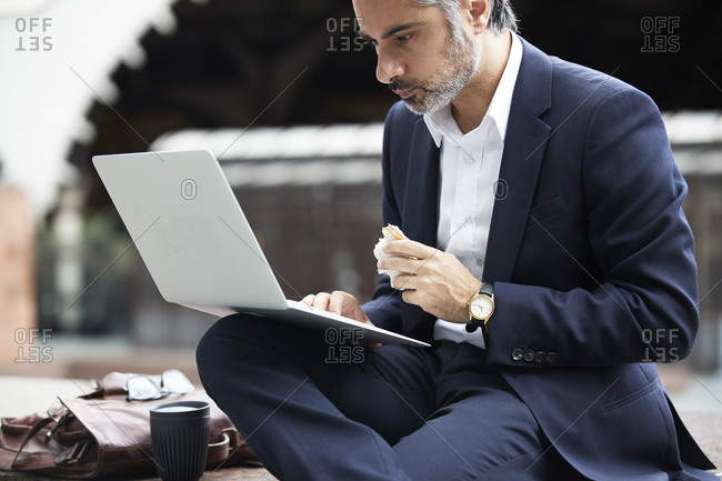 Businessman using laptop while eating food in city