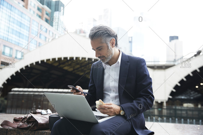 Businessman using phone with laptop while eating food in city