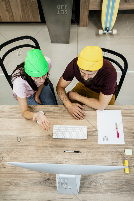 Business couple discussing over computer at desk in modern office
