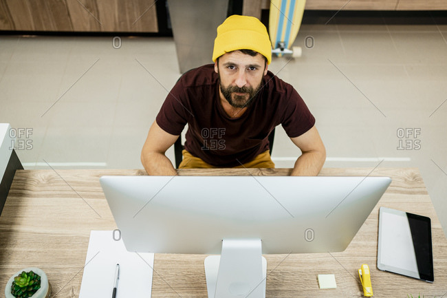 Confident businessman sitting at computer desk in modern office