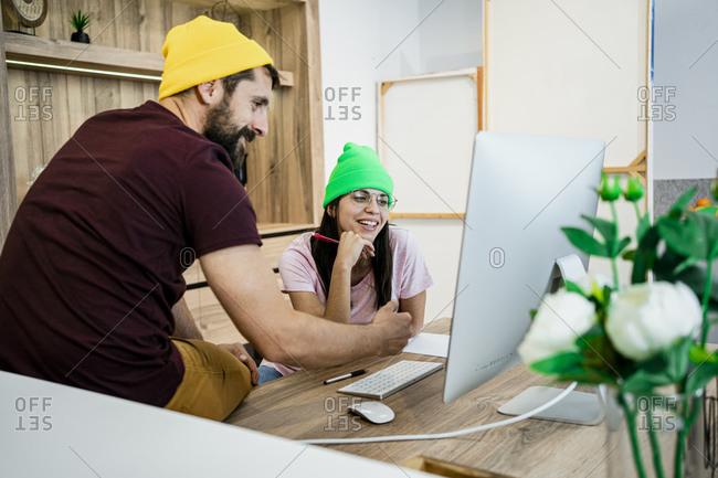 Happy business couple using computer at desk in modern office