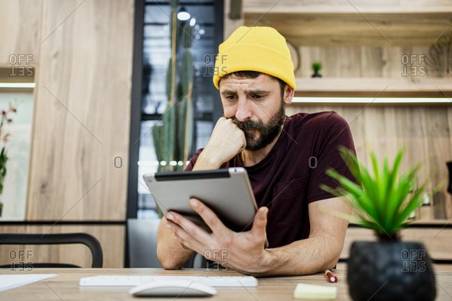Businessman using digital tablet at desk in modern office