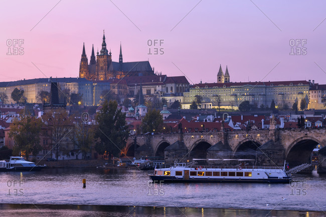 October 31, 2019: Czech Republic- Prague- Charles Bridge stretching over Vltava river at dusk with Prague Castle looming in background