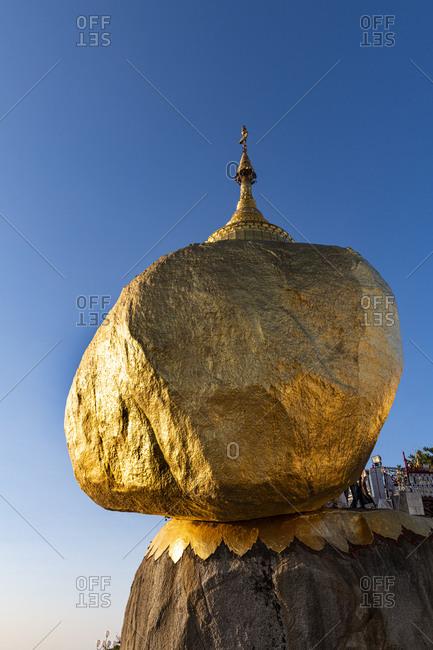 Myanmar- Mon state- Kyaiktiyo Pagoda- Golden rock against blue sky- low angle view