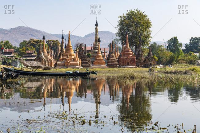 Myanmar- Shan State- Samkar- Stupas of Taw Mwe Khaung Pagoda reflecting in adjacent lake