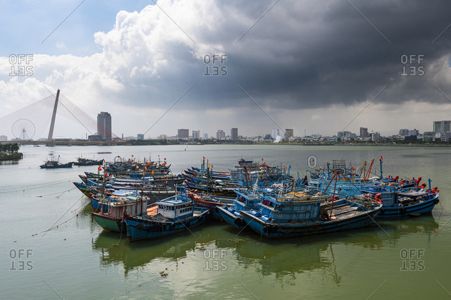 Vietnam- Da Nang- Storm clouds over old fishing boats moored in city harbor