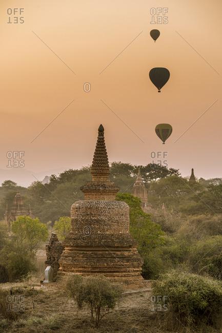 Myanmar- Mandalay Region- Bagan- Hot air balloons flying over ancient stupas at dawn