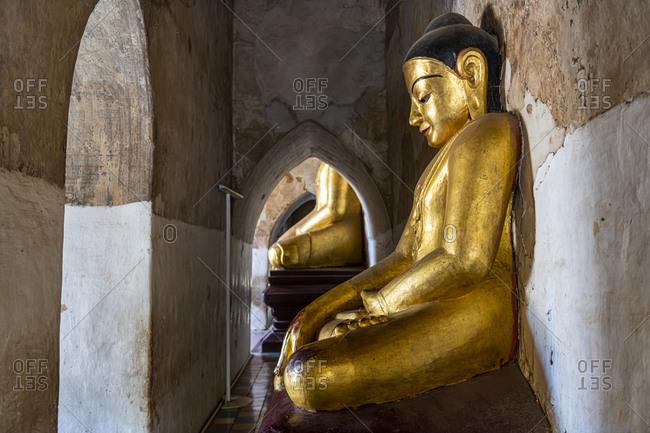 Myanmar- Mandalay Region- Bagan- Gold colored statue of meditating Buddha inside Manuha Temple