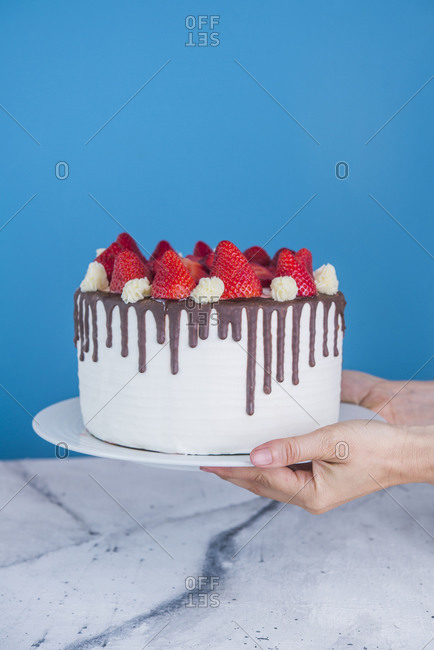 Hands holding cake with icing- chocolate and strawberries