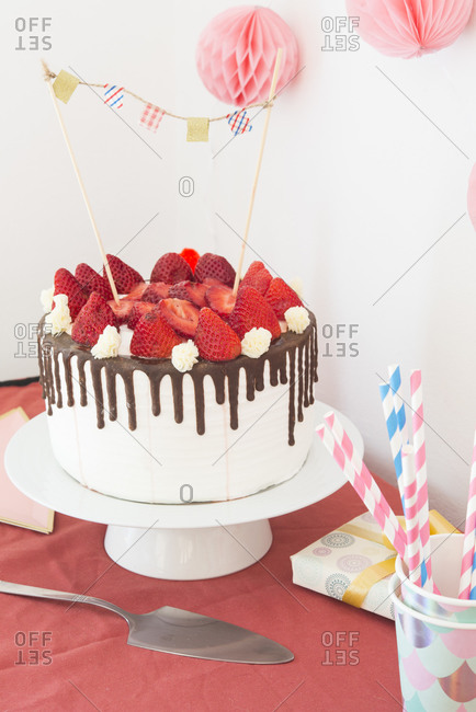 Cake with icing- chocolateand strawberries on party table