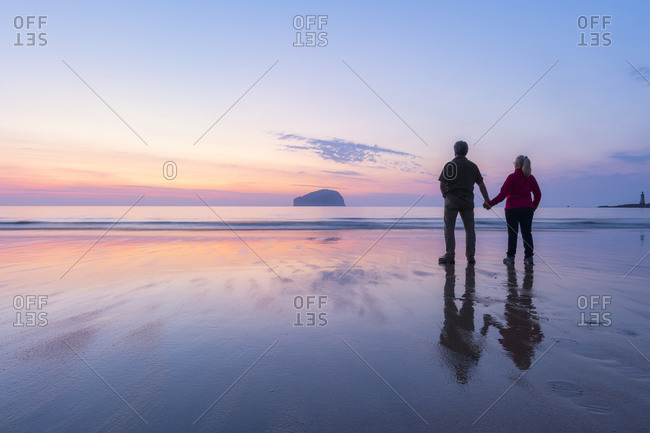 Couple looking at sea while standing on Seacliff Beach- North Berwick- Scotland during sunset