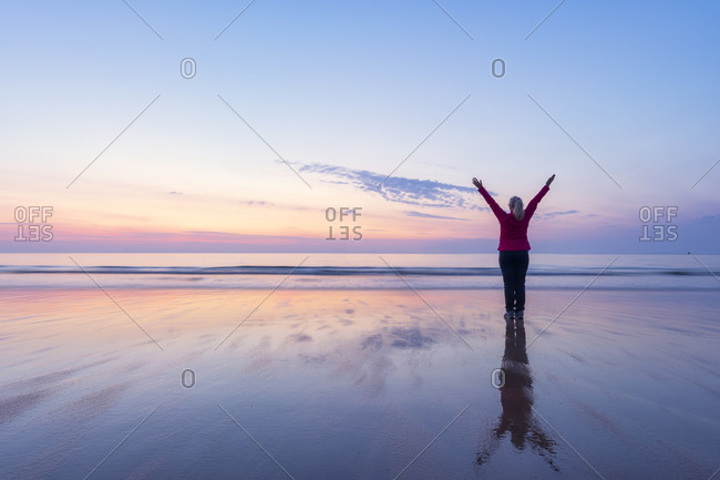 Mature woman with arms raised standing at Seacliff Beach- North Berwick- Scotland during sunset