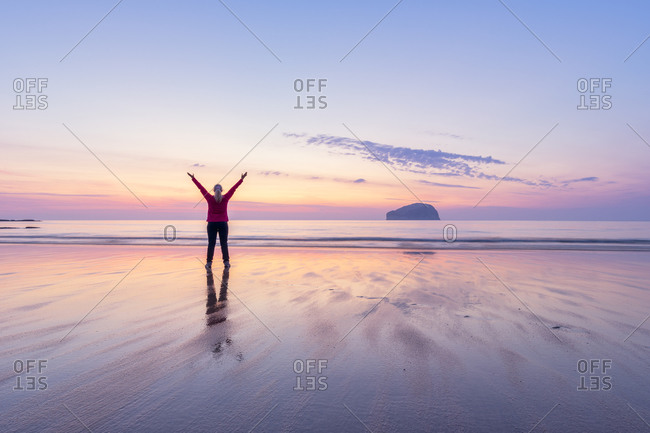 Mature woman with arms raised standing at Seacliff Beach during sunset- North Berwick- Scotland