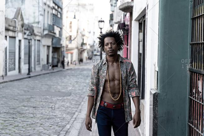 Thoughtful retro man wearing unbuttoned shirt while walking on sidewalk