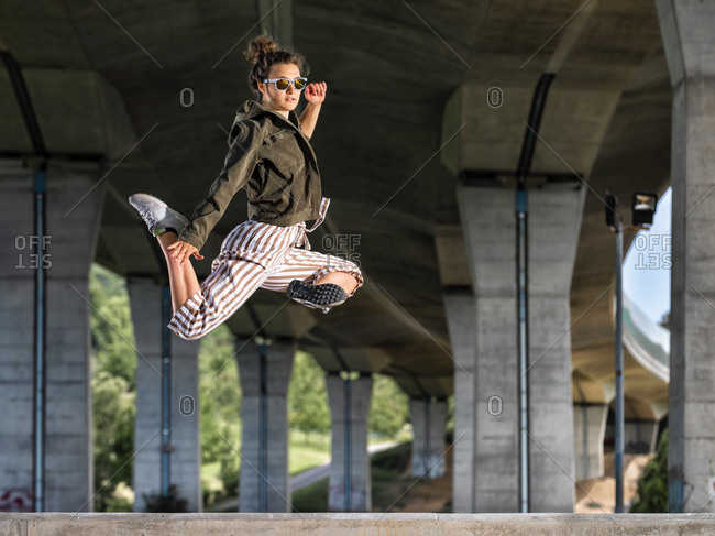 Young woman doing acrobatics and jumping under bridge