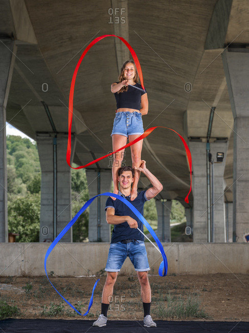 Young couple doing acrobatics with fitness band