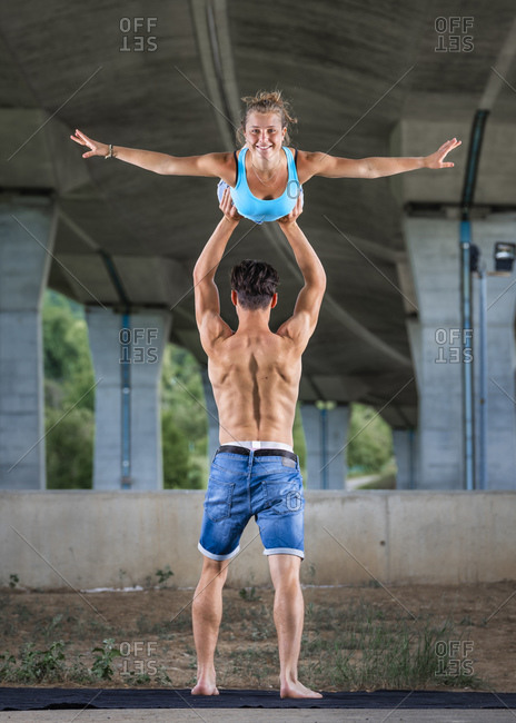 Young couple doing acrobatics outdoors