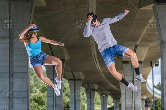 Young couple doing acrobatics under bridge