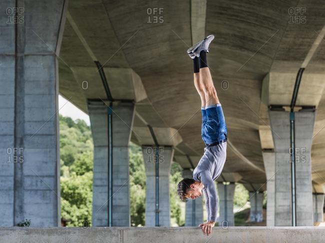 Young man doing acrobatics outdoors