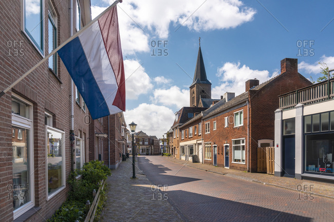 Netherlands- South Holland- Noordwijk- Dutch flag fluttering over empty town street