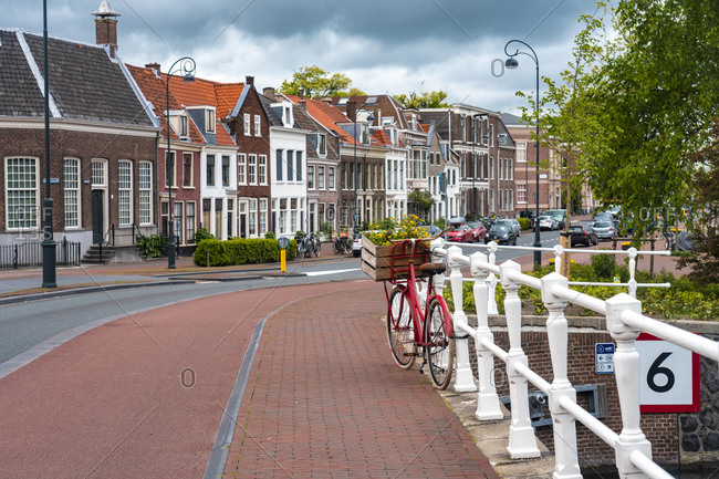 Netherlands- North Holland- Haarlem- Bicycle parked along railing of canal bridge with houses along Hooimarkt street in background