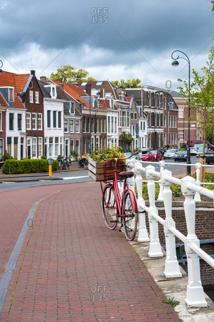 Netherlands- North Holland- Haarlem- Bicycle parked along railing of canal bridge with houses alongHooimarktstreet in background