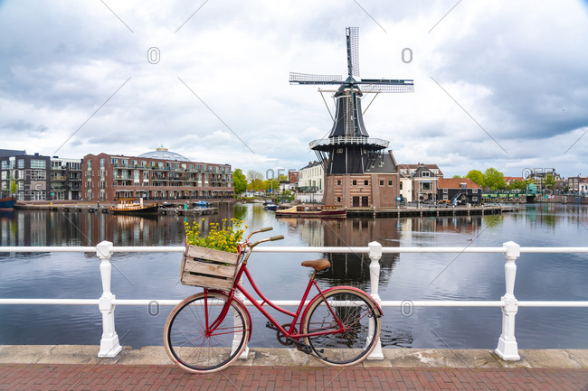 Netherlands- North Holland- Haarlem- Bicycle parked along railing of canal bridge with De Adriaan windmill in background