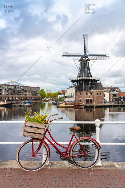 Netherlands- North Holland- Haarlem- Bicycle parked along railing of canal bridgewith De Adriaan windmill in background