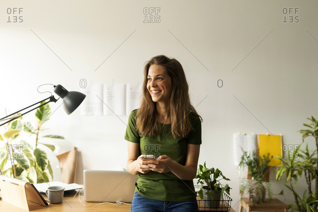 Smiling young woman holding smart phone looking away while standing at desk in home office