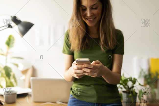 Smiling young woman using smart phone while standing at desk in home office