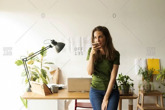 Young woman talking over smart phone while standing at desk