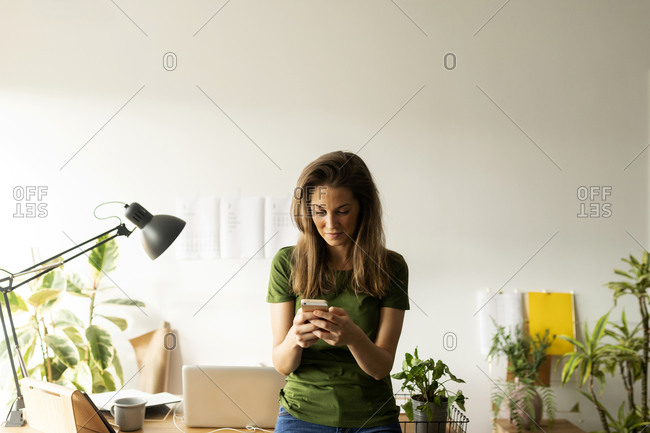 Woman using smart phone while standing at desk in home office