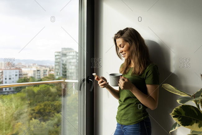 Young woman holding mug using smart phone while standing by window at home