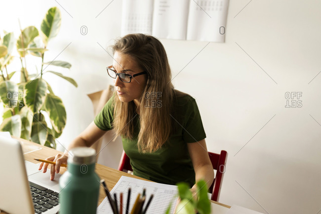 Female entrepreneur using laptop on desk in home office
