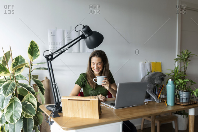 Smiling female entrepreneur holding mug using digital tablet on desk in home office