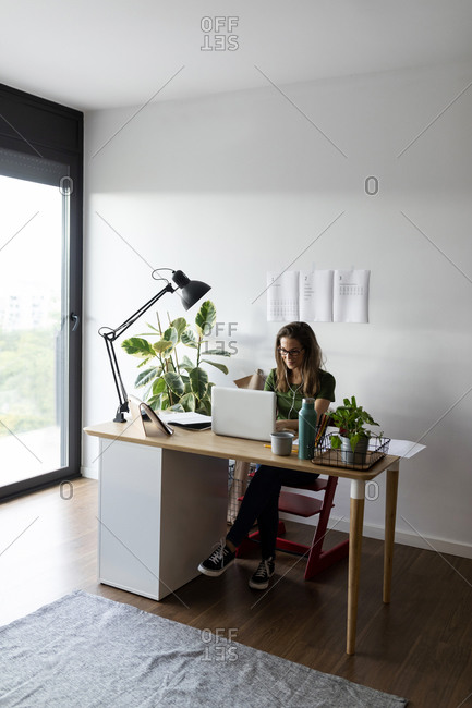 Businesswoman working over laptop on desk in home office