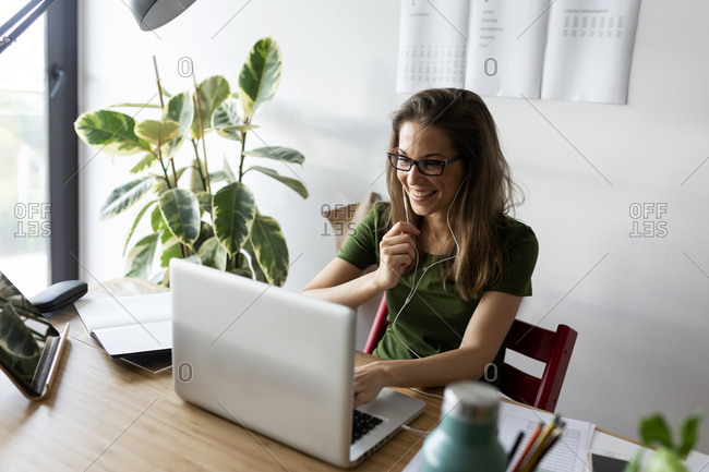 Cheerful female entrepreneur wearing headphones working over laptop on desk at home