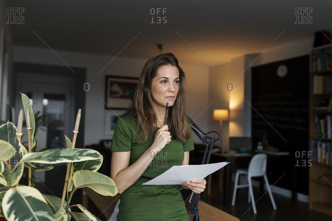 Thoughtful female entrepreneur holding document while standing in home office