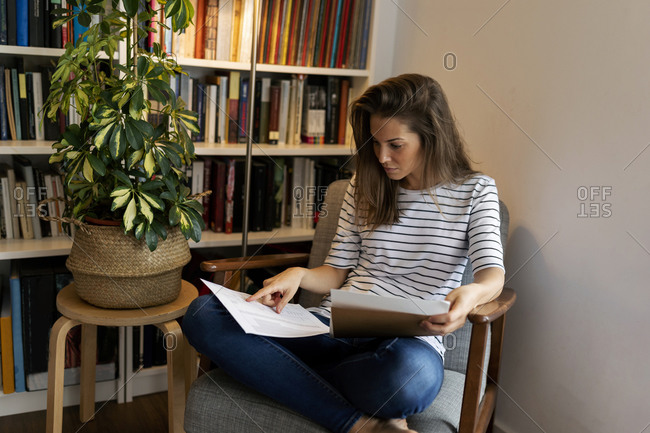 Businesswoman reading document while sitting on chair in home office