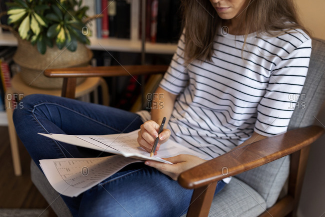 Close-up of businesswoman reading document while sitting on chair in home office