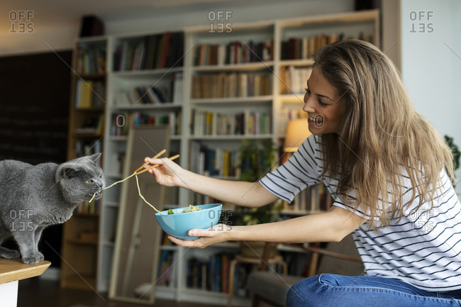 Smiling young woman feeding spaghetti to cat while sitting at home
