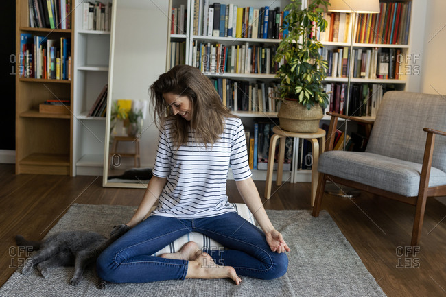 Happy young woman with cat sitting on rug against bookshelf at home