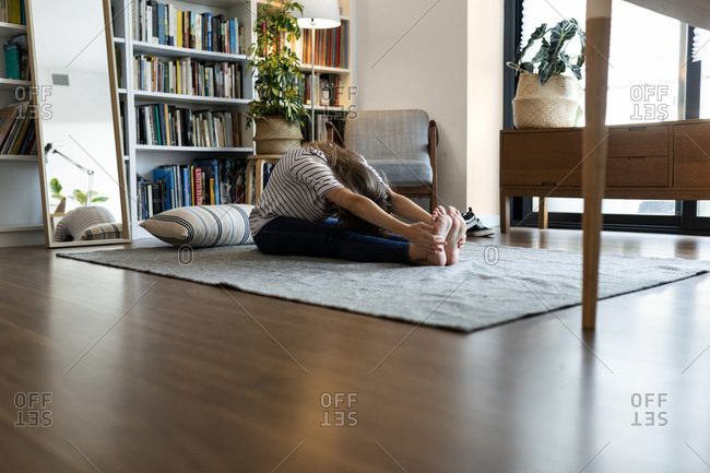 Young woman exercising while sitting on rug at home