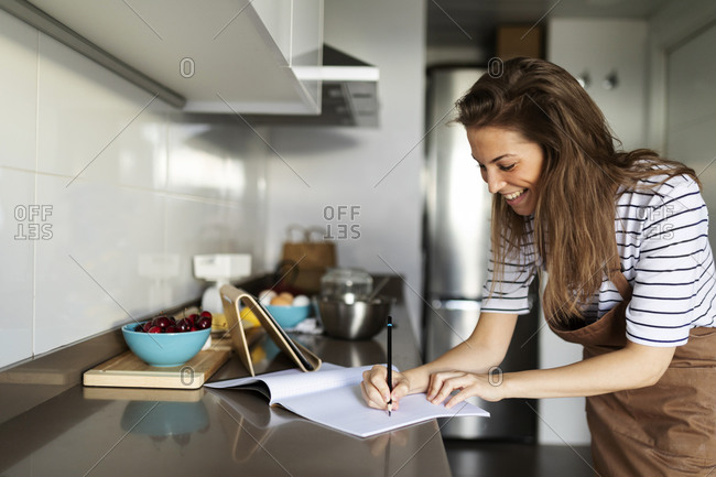 Smiling young woman writing recipe in book while watching video over digital tablet at home